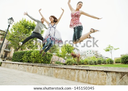 Group of three friends jumping up in the air together while visiting an urban park in the city, having fun and enjoying the energy during a summer day on vacation. - stock photo