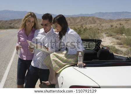 Group of three friends looking at map on street - stock photo