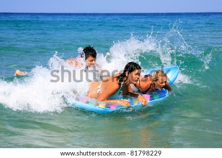 Group of three friends - man and women - on the beach having lots of fun in their vacation in Greece - stock photo