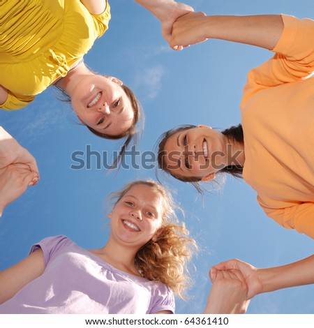 Group of three friends smiling with heads together looking at camera. Low angle view. - stock photo