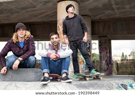 Group of three friends teenagers young men enjoying having fun together and doing sport at a skateboarding park crouching with their skateboards, smiling outdoors. Active young people, lifestyle. - stock photo