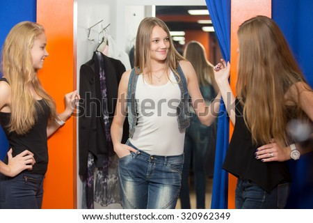 Group of three girlfriends shopping together. Cheerful young beautiful woman wearing jeans and denim vest standing in fitting room in mall, trying casual clothes, showing her new outfit to friends - stock photo