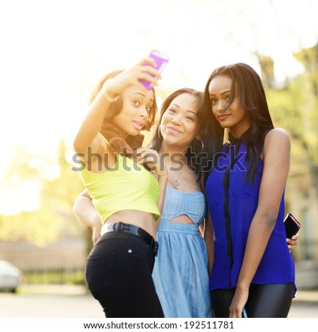 group of three girls wearing bright clothes taking selfies with smart phone - stock photo