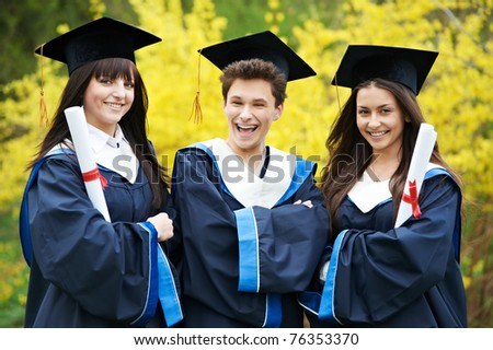 group of three graduation students in the park ? cheerful and happy - stock photo