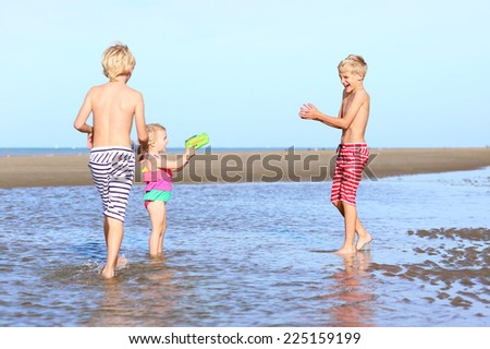Group of three happy active kids, 2 twin brothers and little sister, cute toddler girl in colorful swimming suit, playing on the beach, running and splashing with the water guns at low tide - stock photo