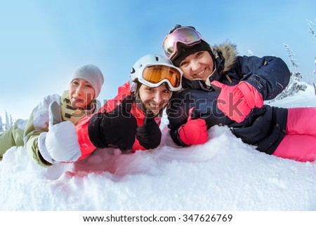 Group of three happy girls snowboarders lies in the snowdrift. Sheregesh resort, Siberia, Russia