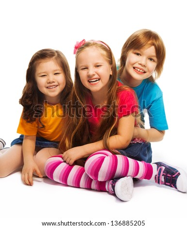Group of three kids, two girls and boy together, happy, laughing, hugging, sitting on the floor isolated on white