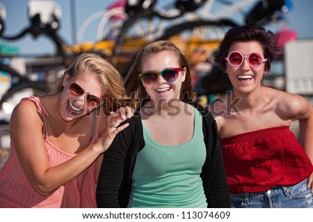 Group of three laughing teenage girls at an amusement park