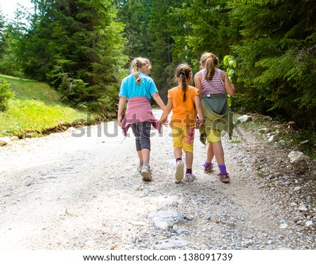 Group of three little girls in the forest