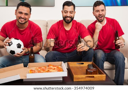 Group of three male friends wearing their favorite soccer team jerseys and watching a game with pizza and beer - stock photo