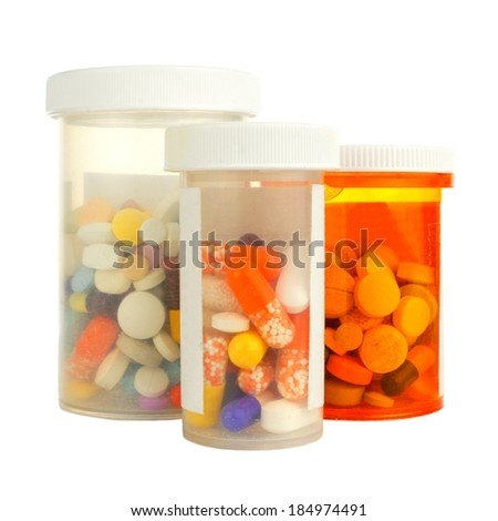 Group of three medicine bottles filled with various pills - stock photo