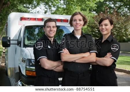 Group of three paramedics standing in front of ambulance with smile - stock photo