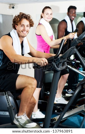 Group of three people exercising their legs, doing cardio training. - stock photo