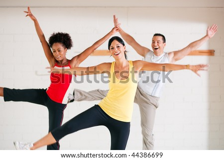 Group of three people in colorful cloths in a gym doing gymnastics - stock photo