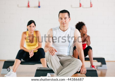 Group of three people in colorful cloths in a gym having a break from their fitness gymnastics exercise sitting on their steppers - stock photo
