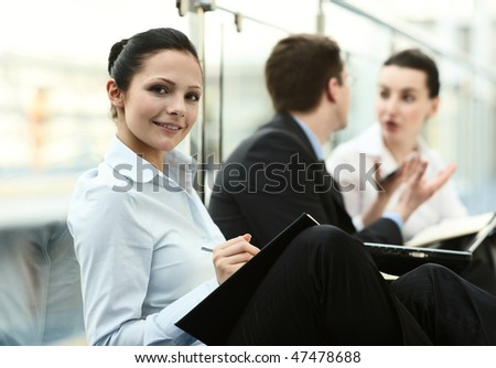 group of three persons talking on the corridor in office space with laptop, potrait