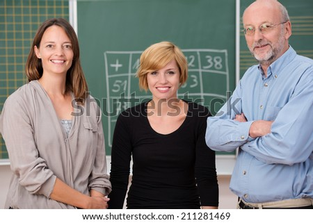 Group of three school teachers with confident friendly smiles standing in front of a class blackboard, one man and two women - stock photo