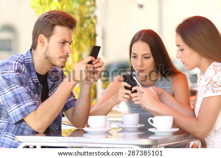 Group of three smart phone addicted friends in a coffee shop terrace everyone with one cellphone - stock photo