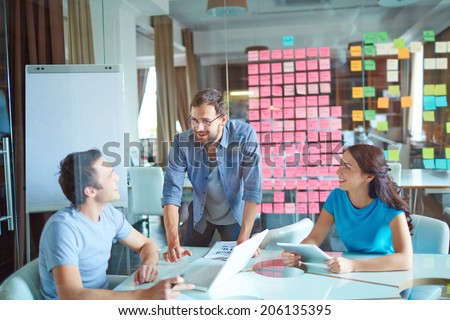 Group of three successful business partners in casual communicating at meeting in office - stock photo