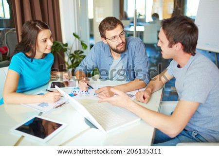 Group of three successful business partners in casual discussing ideas at meeting in office
