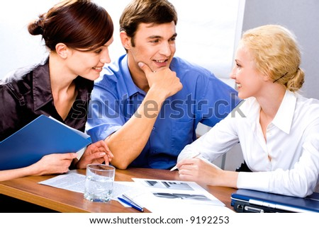 Group of three successful business people discuss working ideas - stock photo