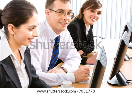 Group of three successful specialists sitting at the table in a line in front of monitors