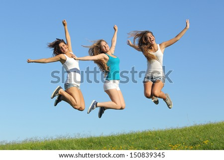 Group of three teenager girls jumping on the grass with the sky in the background             - stock photo