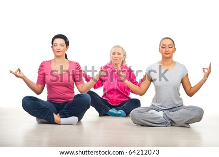 Group of three women in lotus yoga position on floor over white background - stock photo