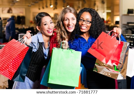 Group of three women - white, black and Asian � shopping downtown in a mall - stock photo