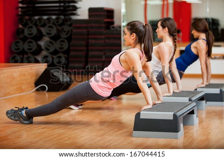 Group of three women working out together in a class at a gym - stock photo