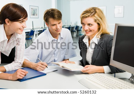 Group of three young business people are discussing new teaching material in the computer room
