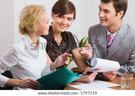 Group of three young business people are discussing new working plan in the office