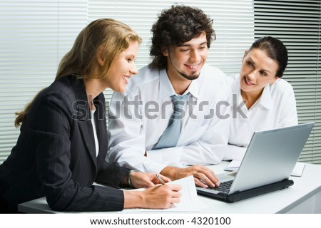 Group of three young business people gathered together around the laptop discussing an interesting idea