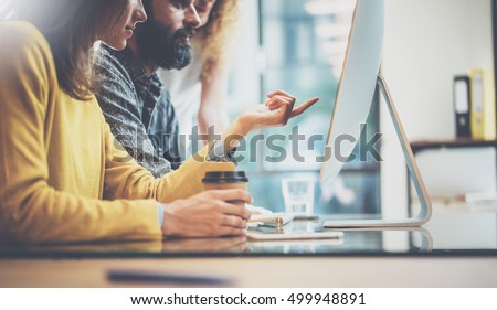 Group of three young coworkers working together in a sunny office.Man typing on computer keyboard.Woman pointing hand to desktop screen.Horizontal image,blurred background