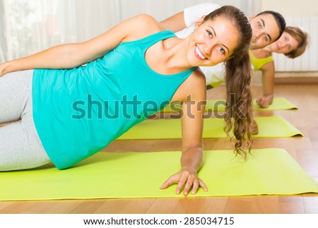 Group of three young people doing exercises in fitness club. Focus on girl - stock photo