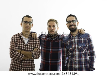 Group of three young people in everyday clothes, posing in the studio, smiling - stock photo