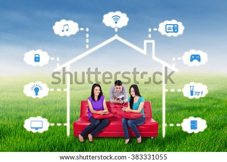 Group of three young people sitting on the sofa while using smartphone to control a smart house technology system, shot outdoors - stock photo