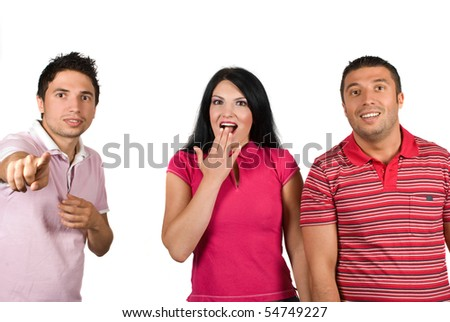 Group of three young people standing in a row and looking very surprised when a boy pointing to something isolated on white background - stock photo
