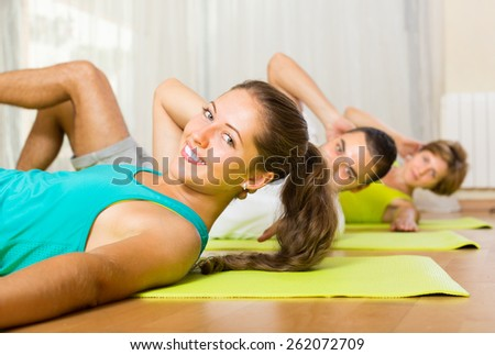 Group of three young people training in fitness club. Focus on girl