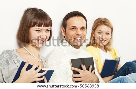 Group of three young smiling people, each person holding a book