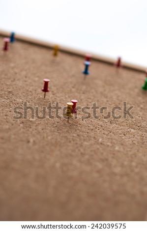Group of thumbtacks pinned on corkboard. - stock photo
