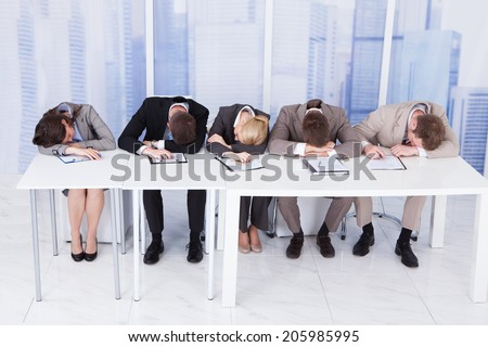 Group of tired corporate personnel officers sleeping at table in office - stock photo