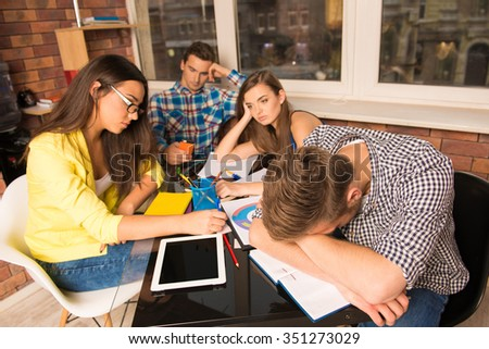 Group of tired students working hard together - stock photo