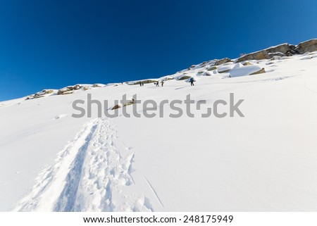 Group of tour skier hiking uphill on a steep snowy slope. Ski tracks in powder snow, clear blue sky, winter season. Unrecognizable people. - stock photo