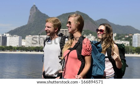Group of tourist backpackers friends  walking through Rio de Janeiro with Christ the Redeemer in background. - stock photo