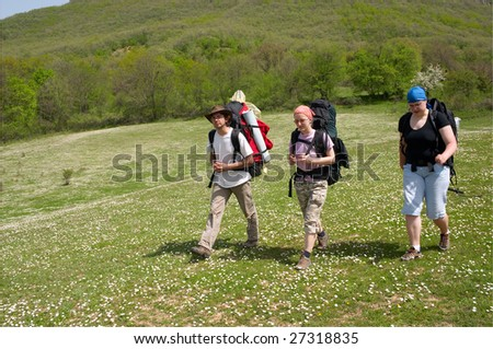 Group of tourist with backpack walking on the meadow