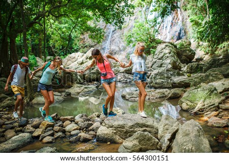 group of tourists holding hands crossing jungle stream in thailand