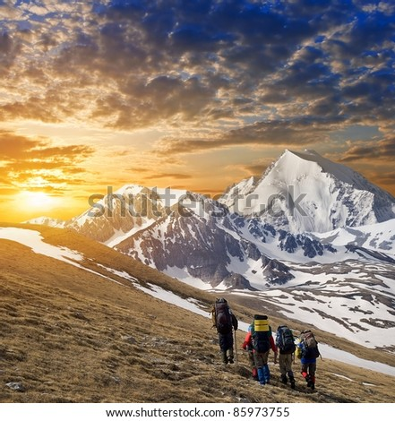 group of tourists in a hike on a mountain slope - stock photo