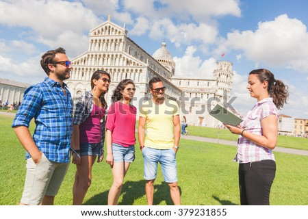 Group of tourists in Pisa, Italy. A group of friends is listening to a guide talking about a famous monument. They are a multicultural group on holidays, with travel and architecture concepts - stock photo