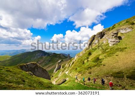 Group of tourists on mountain, in spring season - stock photo